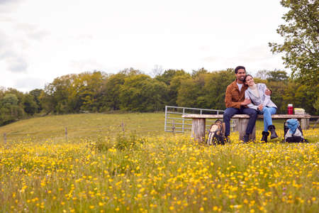 Couple On Walk In Countryside Sit On Bench And Enjoy Picnic Together Standard-Bild