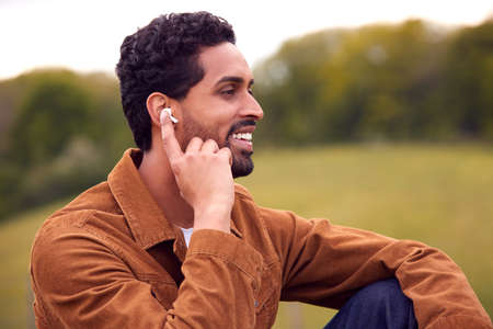 Man Sitting On Bench In Countryside Relaxing And Listening To Music Or Podcast On Wireless Earphones Standard-Bild