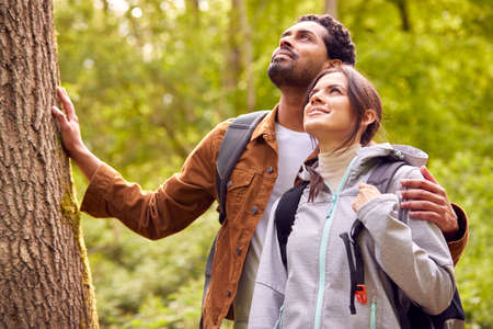 Couple Hiking Along Path Through Forest In Countryside Taking A Break And Resting Against Tree Standard-Bild