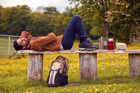 Man Lying On Bench In Countryside Relaxing And Listening To Music Or Podcast On Wireless Earphones Standard-Bild