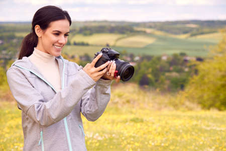 Woman With Digital DSLR Camera Taking Photos In Countryside