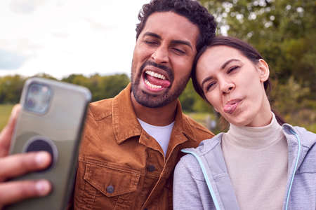 Couple On Walk In Countryside Pulling Funny Faces As They Take Selfie On Mobile Phone Standard-Bild