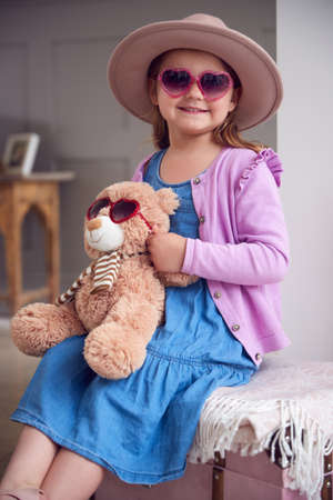 Portrait Of Young Girl Wearing Hat And Sunglasses Having Fun Playing With Dressing Up Box At Home