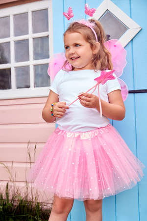 Young Girl Wearing Fairy Costume Playing Outdoors In Garden By Playhouse Standard-Bild