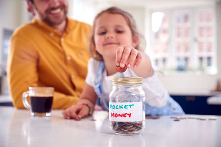 Father And Daughter Putting Pocket Money Into Savings Jar On Kitchen Counter Standard-Bild