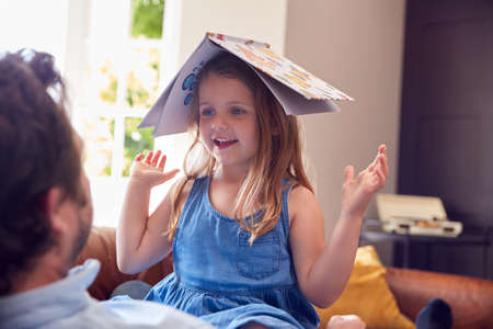 Father And Daughter Lying On Sofa At Home As Girl Puts Reading Book On Head