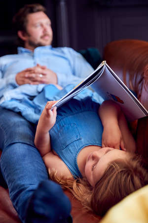 Father And Daughter Lying On Sofa At Home As Girl Reads Book