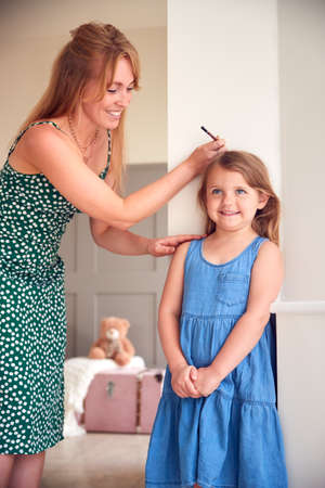 Mother Measuring Daughter's Height And Marking On Wall At Home