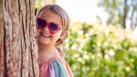 Smiling Young Girl Wearing Sunglasses Playing Hide And Seek Behind Tree In Garden Standard-Bild