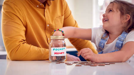 Close Up Of Father And Daughter Counting Pocket Money In Jar On Kitchen Counter
