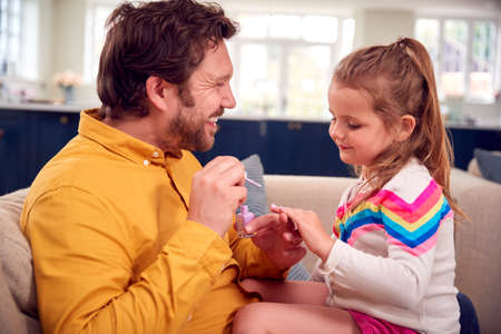 Father Painting Young Daughter's Nails As They Sit On Sofa Together Standard-Bild