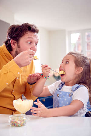 Father And Daughter In Kitchen Eating Ice Cream Dessert With Spoon