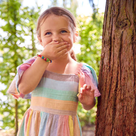 Smiling Young Girl Playing Hide And Seek Behind Tree In Garden Standard-Bild