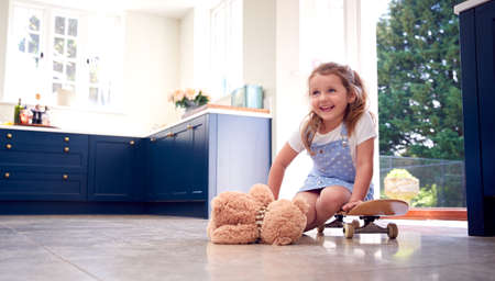 Smiling Young Girl Playing Game Sitting On Skateboard With Teddy Bear At Home