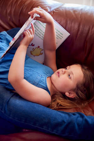 Close Up Of Father And Daughter Lying On Sofa At Home As Girl Reads Book