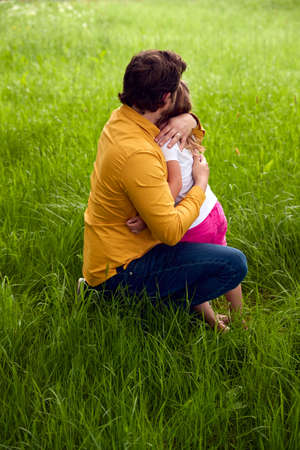 Loving Father Cuddling Young Daughter As They Walk Through Field Together Standard-Bild