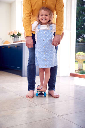 Father Helping Daughter To Balance On Skateboard Indoors At Home