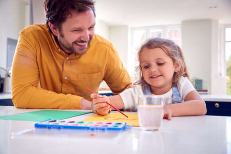 Father And Daughter Painting Picture On Kitchen Counter Standard-Bild