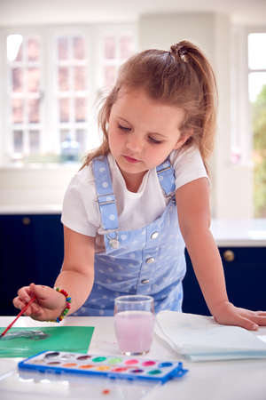Young Girl Painting Picture At Home On Kitchen Counter
