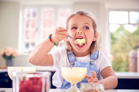 Young Girl In Kitchen Eating Ice Cream Dessert With Spoon Standard-Bild