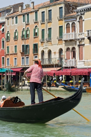 A gondoliere at the Grand Canal in Venice, Italy  Gondolas are the typical boats in Venice and a tour in such a boat is a highlight of an touristic visit  Stock Photo