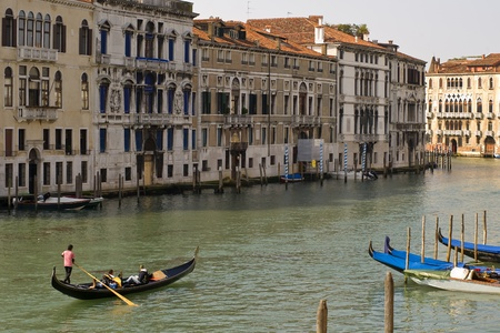 A gondolier with tourists in this gondola at the Grand Canal in Venice, Italy  Gondolas are the typical boats in Venice and a tour in such a boat is a highlight of an touristic visit  Stock Photo
