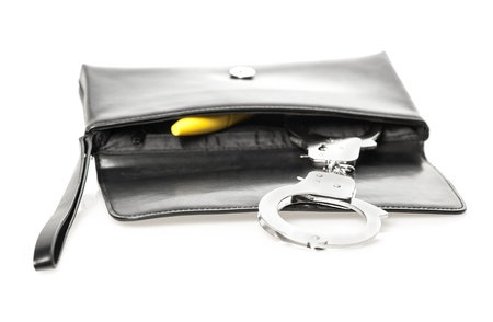 An open black clutch bag/purse with handcuffs and a yellow dildo. Stock Photo - 16761477