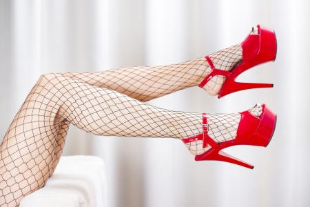 Legs of a woman wearing fishnet stockings and red platform shoes