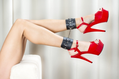 Female lages with black ankle cuffs and red fetish high heels with platform