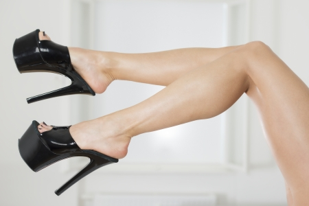 Legs of a woman wearing black platform high heels shoes   Stock Photo