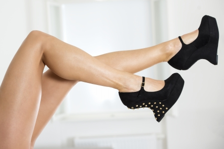 Long and sedy female legs with with black fetish high heels with platform, wedge sole in curve style and ankle-strap and metal spikes.