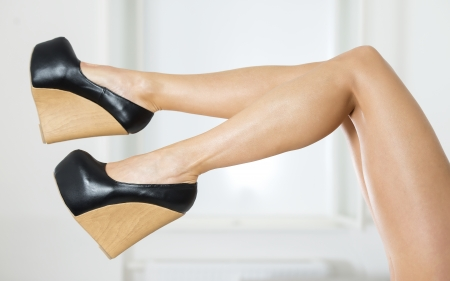 Long and sexy legs in extreme platform shoes in black patent leather and wood pattern;