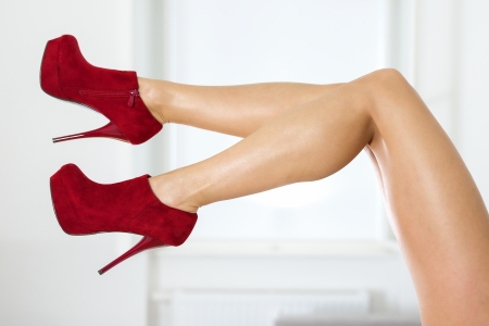 Long and sexy female legs with red ankle boots.