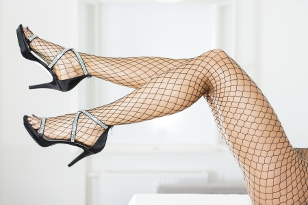 Legs of woman wearing blick fishnet stockings and elegant high heels sandals with rhinestones. Stock Photo