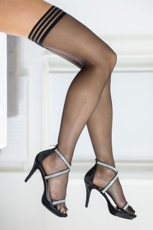 Legs of woman wearing black stockings and elegant high heels sandals with rhinestones. Stock Photo