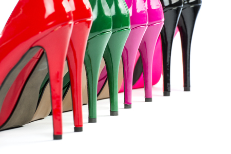 Details of the heels of four pairs of colorful high heels shoes.  Stock Photo