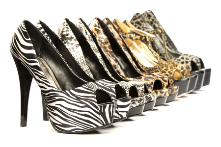 A group of five high heels shoes in various animal print designs;