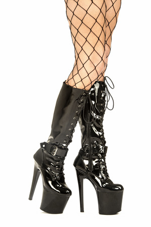 Sexy female legs in fishnet stockings and shiny black fetish boots with extrem platform sole.