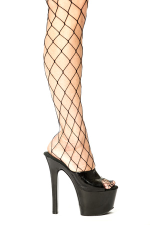 Sexy female legs in fishnet stockings and shiny black fetish high heels with extrem platform sole.