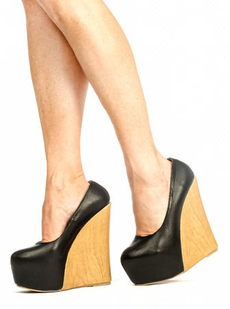 Sexy female legs in black high heels with wooden wedge sole;