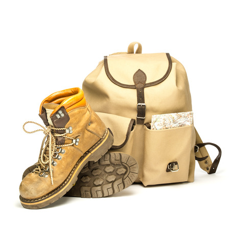 studio shot of vintage hiking boots, a vintage backpack made of canvas and an old map.