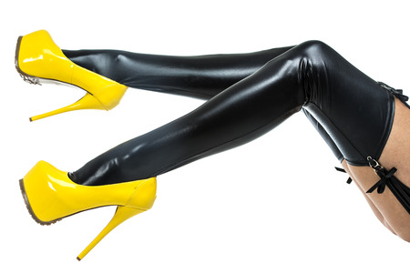 Legs of a woman in fetish wear: latex stockings with garter belt and high heel shoes with extrem platform.