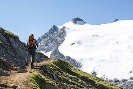 Sportive woman in her 30s is hiking in the Austrian Alps, in the background high peaks and glaciers. Location: Ötztal, Tirol, Austria, close to the border to South Tyrol, Italy.