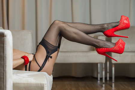 Sexy long legs of a caucasian woman wearing garter belt and black stockings.With red high heels shoes and a red