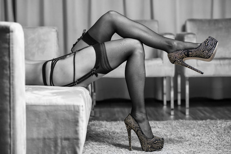 Sexy long legs of a caucasian woman wearing garter belt and stockings.With high heels shoes with golden rhinestones.