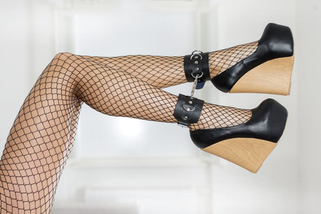 Long and sexy legs wearing fishnet stockings and extreme platform shoes in black patent leather and wood patternthe legs are cuffed. Stock Photo