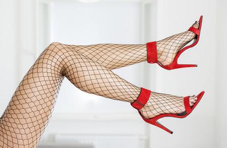 black sex: Legs of woman wearing blick fishnet stockings and elegant high heels sandals in red.