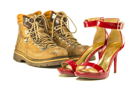 heel strap: Extremes meet: mens working or hiking boots in a vintage look and in contrast to them a pair of shiny fancy red high heels shoes with ankle strap small platform and stiletto.