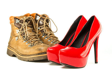 Extremes meet: mens working or hiking boots in a vintage look and in contrast to them a pair of shiny fancy red high heels shoes with inner platform and stiletto.