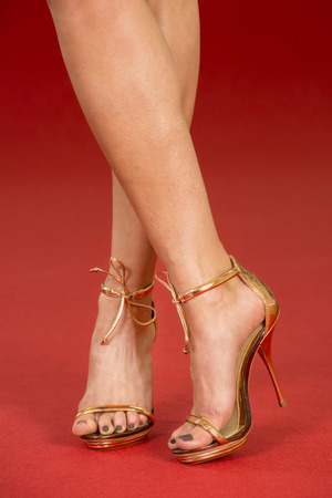 red carpet: Sexy legs of a woman wearing golden high heels shoes on a red carpet. Stock Photo